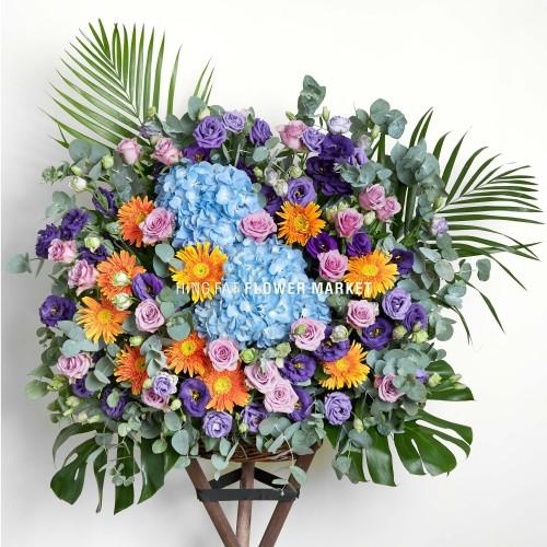 Blue hydrangea and orange gerbera flower stand